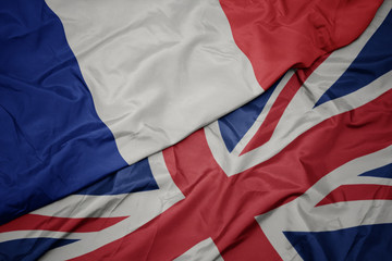 waving colorful flag of great britain and national flag of france. Wall mural