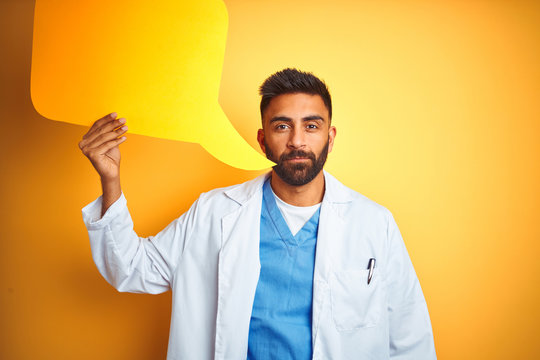 Young indian doctor man holding speech bubble standing over isolated yellow background with a confident expression on smart face thinking serious