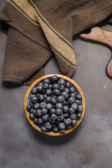 Fresh blueberries in ceramic bowl and brown cloth