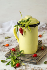 Vitamin drink of rose hips in a high yellow mug on an old wooden table. Selective focus.