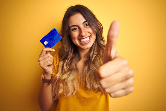 Young beautiful woman holding credit card over yellow isolated background happy with big smile doing ok sign, thumb up with fingers, excellent sign