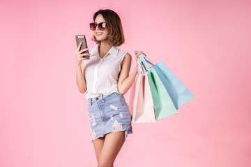 Asian pretty young woman walking over pink  pastel background. She smiling and  holding shopping bags. she nice-looking lovely attractive shine She holding mobile. Wall mural
