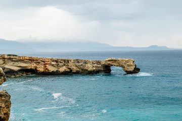 Rock in the form of a stone arch on the coast of Crete in the Mediterranean sea