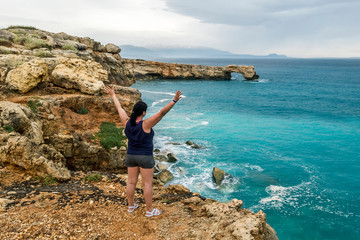 girl stands on the edge of a cliff with arms outstretched and looks into the distance at sea