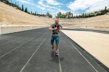 Athlete running on the track at the Panathenaic stadium.
