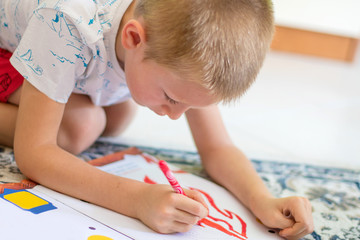 young boy is drawing on the floor at home
