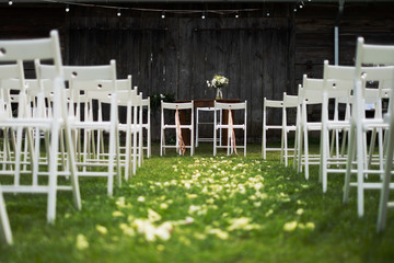 Wooden barn decorated by white cloth and flowers with greenery standing in the center of wedding ceremony. white chairs on side.