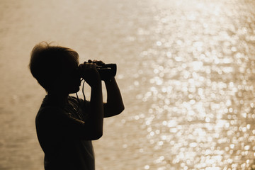 Closeup view of black silhouette of little kid standing outdoor at blurry golden river water...
