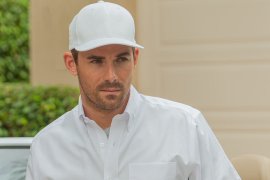 Closeup photo of a handsome entrepreneur wearing a white baseball cap and a white button-down shirt. The man looks away to his left focused on something in the distance.