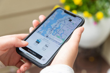 Hands hold iPhone XS Max while viewing Uber application in Everett, Washington on July 22, 2019