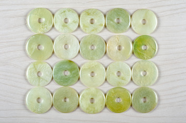 Twenty butter jade round donut-shaped stones are stowed four rows. Five pieces in each one. Top view.