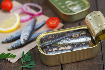 Can of sardines served with cherry tomato, lemon and onion rings. Preserved sea fish.
