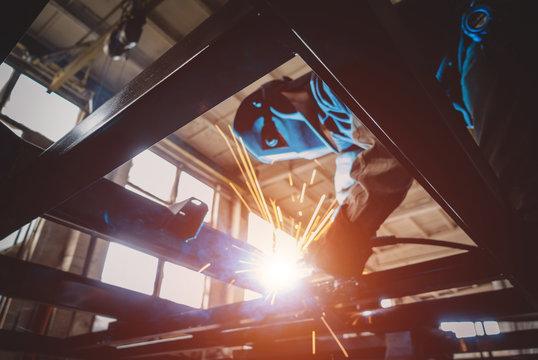 Welder welds metal frame of car