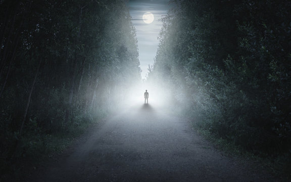 Silhouette of a man in a dark and foggy forest