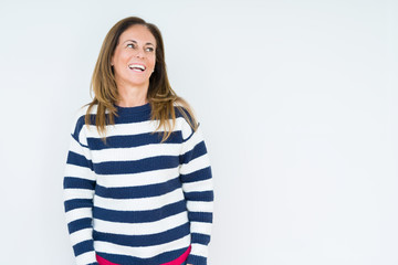 Beautiful middle age woman wearing navy sweater over isolated background looking away to side with smile on face, natural expression. Laughing confident.