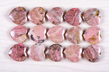 Three rows of rose-pink rhodonite heart-shaped stones on white wooden background