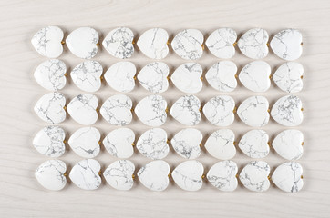 Five rows of white howlite heart-shaped stones on white wooden background