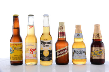 IRVINE, CA - JUNE 14, 2015: Popular Mexican Beers. Pacifico, Sol, Corona, Bohemia and Modelo beer bottles on a wet table with reflections.