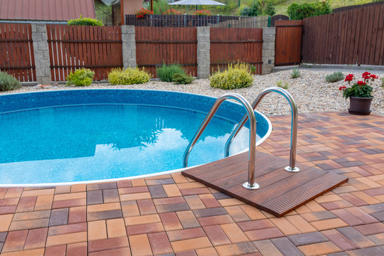 small home swimming pool with two black sun loungers