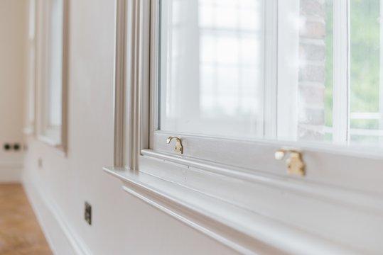 Closeup shot of a gold sash lock on a white window