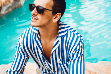 Portrait of a handsome young man in a striped shirt and sunglasses. Perfect hair & skin. Summer vacation concept. Outdoor shot.