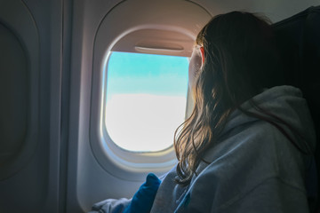 Girl looking out window of airplane in flight