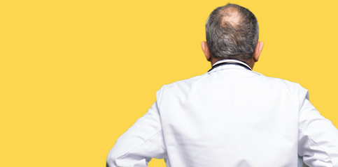 Handsome senior doctor man wearing medical coat standing backwards looking away with arms on body
