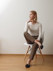 Fashionable girl in a white sweater and checkered pants . Natural lifestyle portrait of girl , emotional and fashion mood ,chic clothes and summer theme . Soft warm vintage color tone . Gold earrings