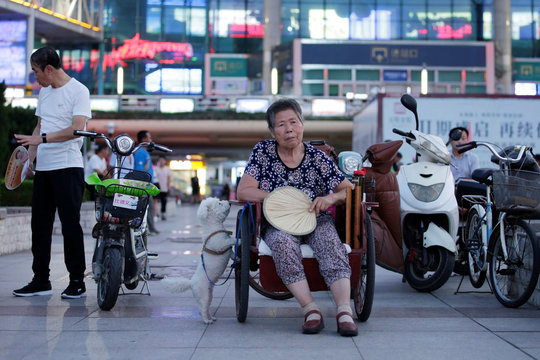 A 68-year-old woman with a stroke sits in a tricycle as she rests at a city square in Weifang