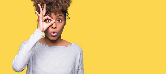 Obraz Beautiful young african american woman over isolated background doing ok gesture shocked with surprised face, eye looking through fingers. Unbelieving expression. - fototapety do salonu