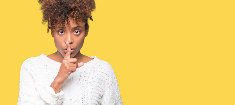 Beautiful young african american woman wearing winter sweater over isolated background asking to be quiet with finger on lips. Silence and secret concept.