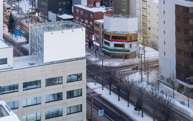 Blank billboard for outdoor advertising on top office building in Business area on background, Japan.