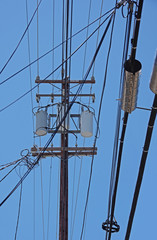 Electricity distribution pylon with wiring cables and electrical equipment seen against a bright blue sky