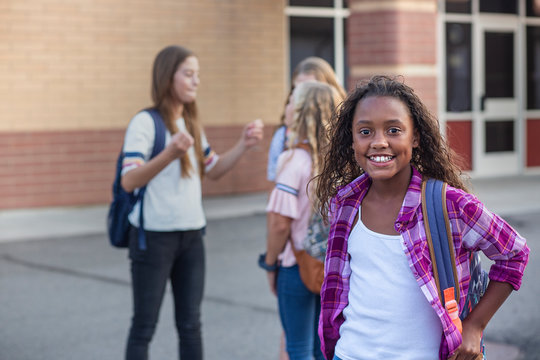 Cute, diverse pre-adolescent teen student hanging out with friends after school. Selective focus on the smiling girl student standing outside the school building