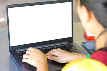 Mock up image of a business woman using and typing on keyboard laptop with blank white desktop screen on work table.