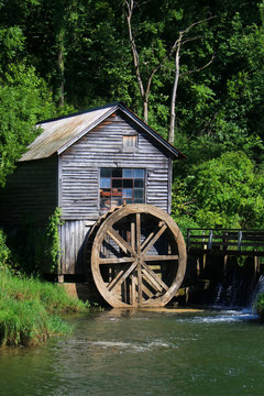 Rural landscape with abandoned watermill in forest. Scenic summer countryside scene with close up vertical view of old wooden water mill and wheel, green trees around it in sunlight. Midwest USA, Wi.
