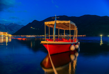 Sunset view of Kotor Bay, mountains and a docked boat in the postcard perfect town of Perast, Montenegro, long exposure