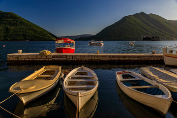 Boats docked in the postcard perfect town of Perast in Kotor Bay at sunset with mountains in the background, Montenegro