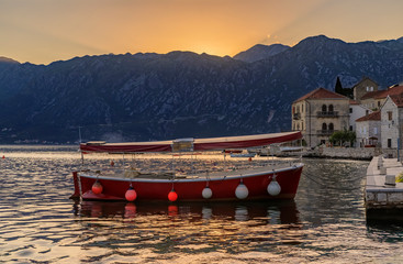 Boat docked in the postcard perfect town of Perast in Kotor Bay with sun setting behind the mountains, Montenegro