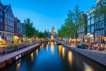 Saint Nicholas Church with Amsterdam skyline at night in Netherlands