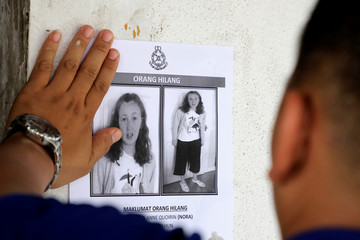 A police officer paste a photo of 15-year-old Irish girl Nora Anne Quoirin who went missing from a resort on a wall at a shop in Seremban.