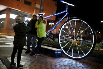 A girl takes a picture next to a bicycle decorated with lights, during a night cycling event in Bogota,