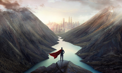 Businessman in a suit and cape hero on top of the hill watching wonderful scenery in mountains with lake during dramatic sunrise .Business ambition and success concept.