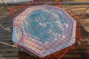 Round outdoor hydromassage bath with bubbling water on the deck of a cruise ship. Closed with a net for the night. View from above.
