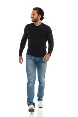 Smiling Man Black Jersey, Jeans And Sneakers Is Walking Towards Camera And Looking Away