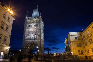 Blurred motion of people near the illuminated Old Town Bridge Tower and statue of Charles IV at the Old Town in Prague, Czech Republic, in the evening.
