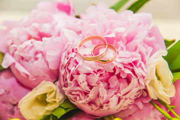 Beautiful delicate wedding bouquet of pink peonies and wedding rings of the bride and groom.