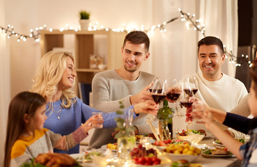 celebration, holidays and people concept - happy family having dinner party, drinking red wine and...