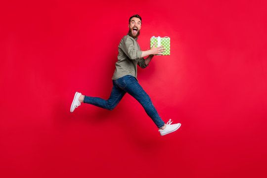 Full length body size photo of rejoicing man wearing jeans denim having received gift at lottery luckily while isolated with red background