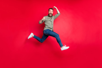 Fototapeta Full length body photo of bearded strong sporty handsome white man wearing grey t-shirt running somewhere with victory while isolated with red background obraz